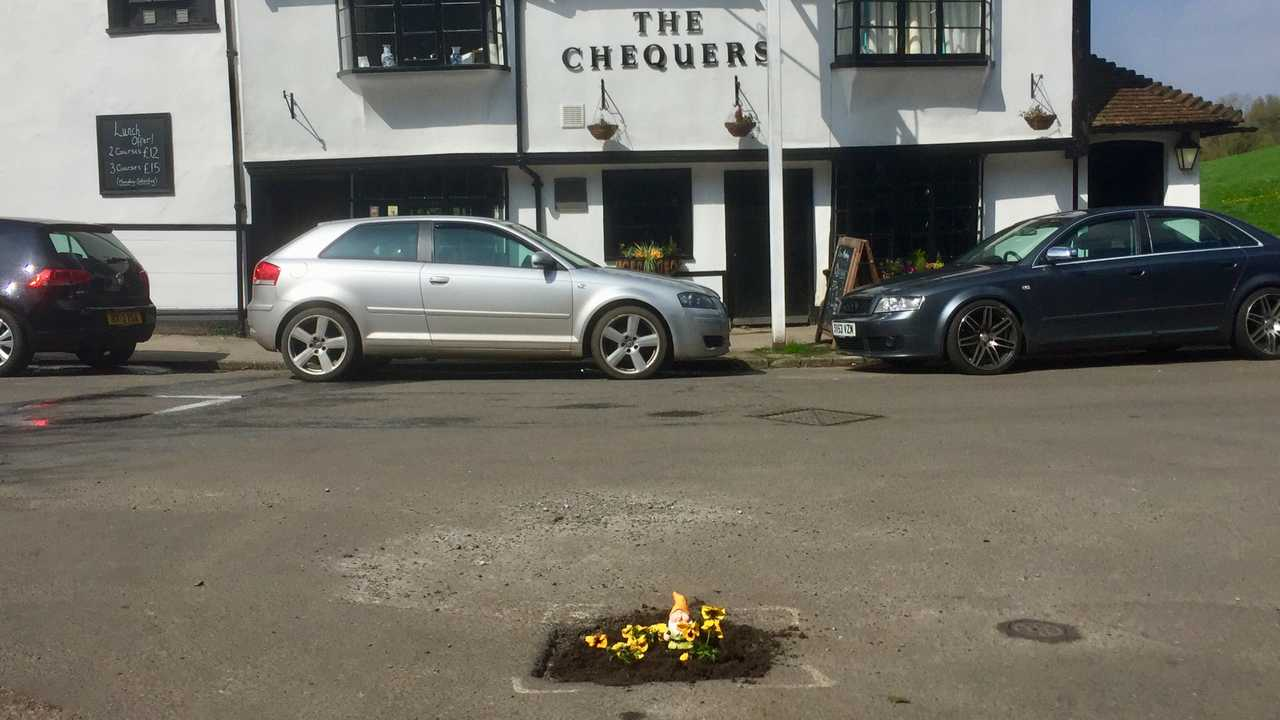 Pothole in the village of Loose has flowers planted in it Maidstone Kent UK