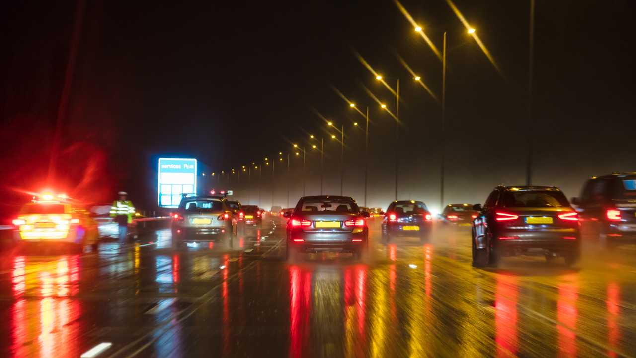 British motorway traffic at night in the rain with police car