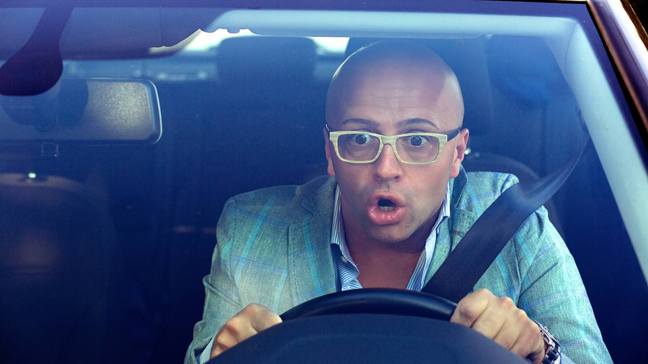 Man driving looking extremely shocked