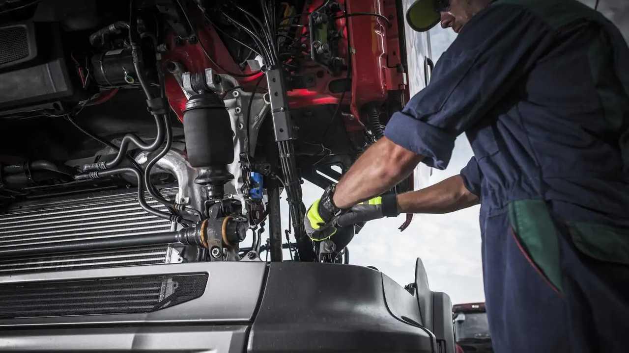 Mechanic repairing broken semi truck engine