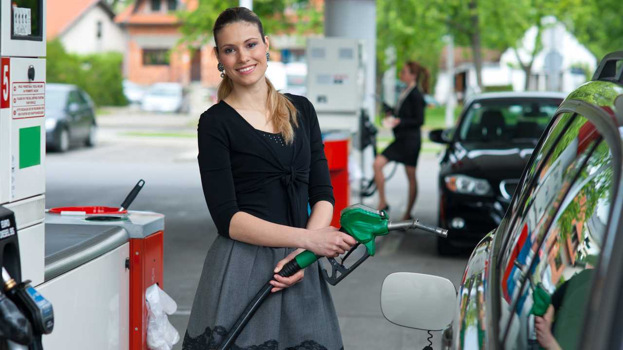 Woman holding fuel pump nozzle at petrol station
