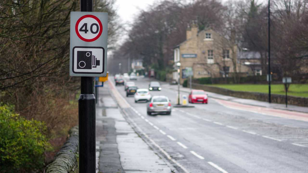 Speed limit sign with speed camera warning on a road in Leeds UK