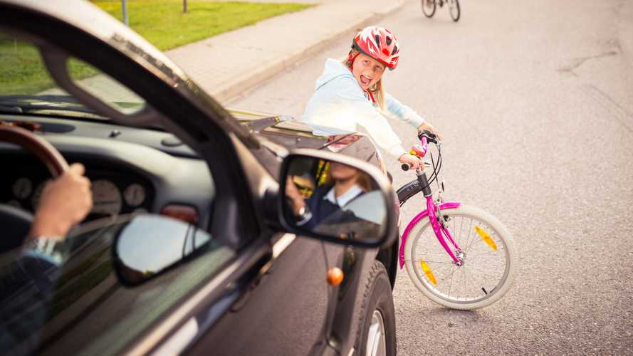 Young girl on bicycle crosses the road in front of a car