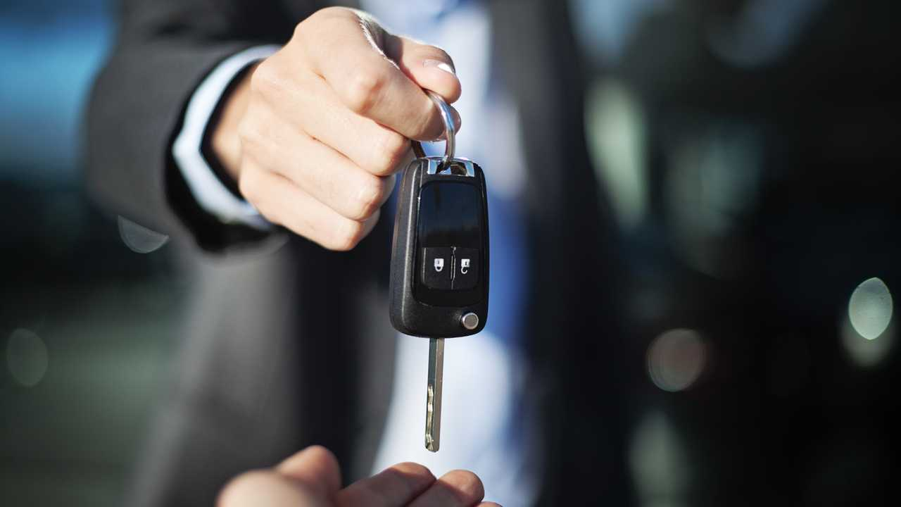 Car salesman handing car keys to woman
