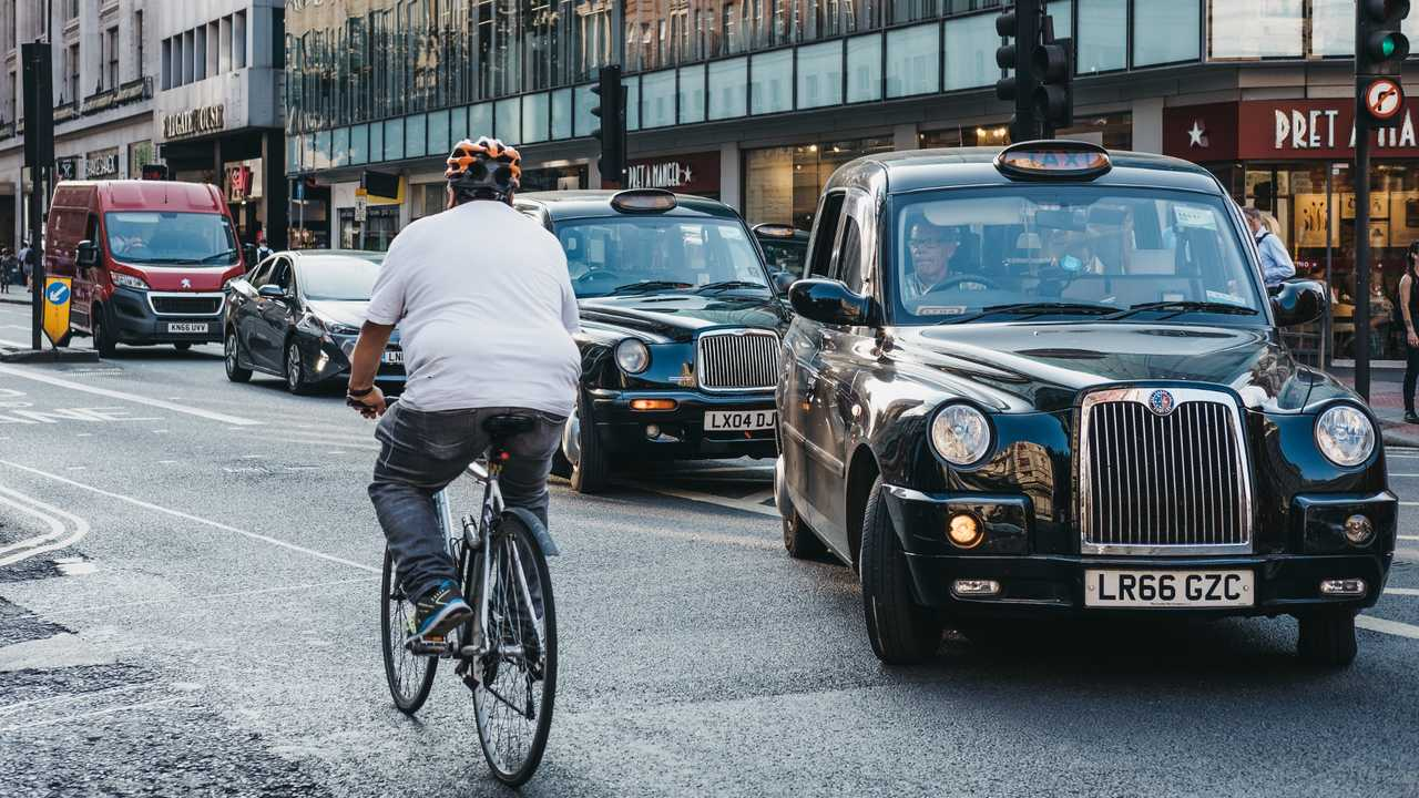 Cyclist going past taxis waiting to turn on Oxford Street in London