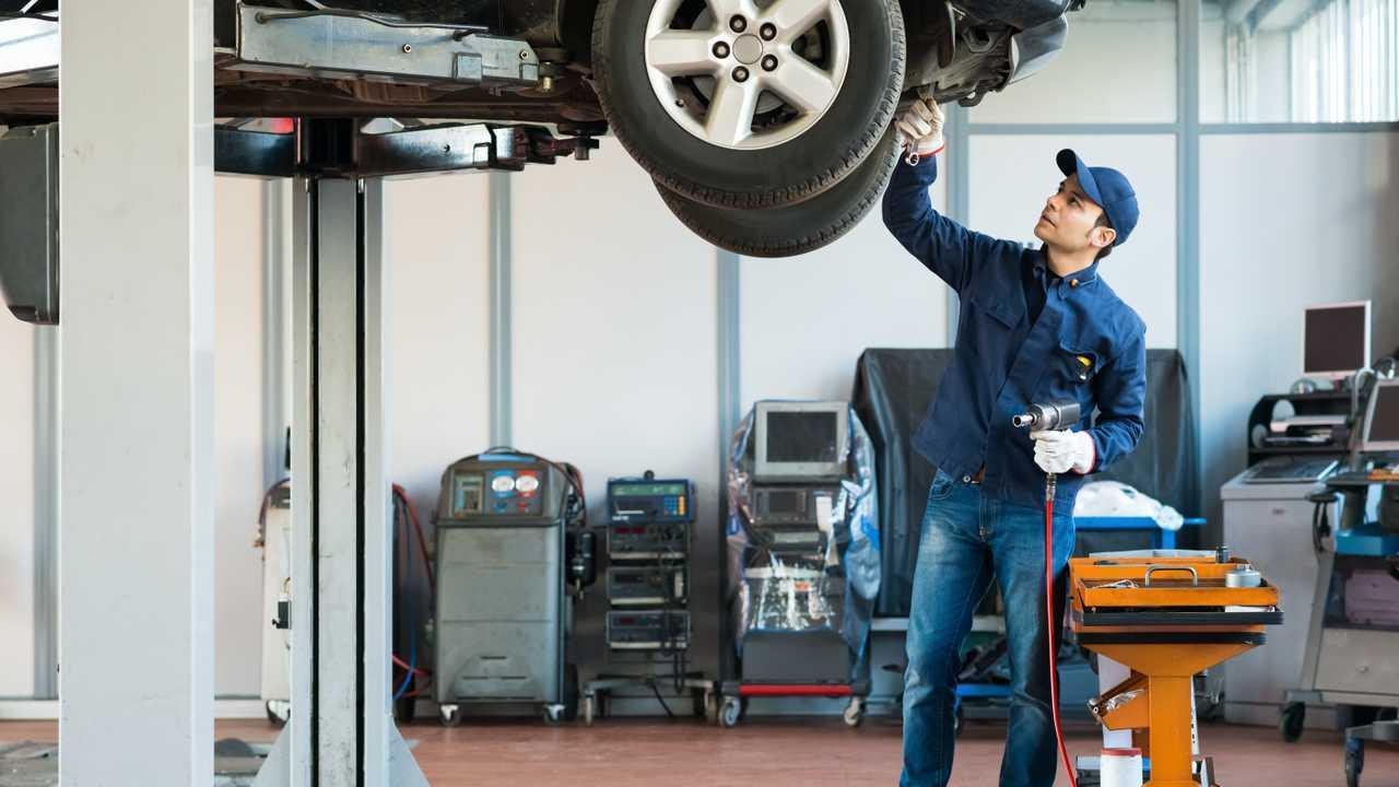 Mechanic working on vehicle on lift