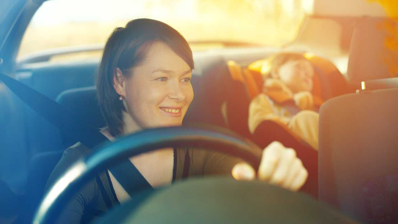 Child in safety seat with mother driving car