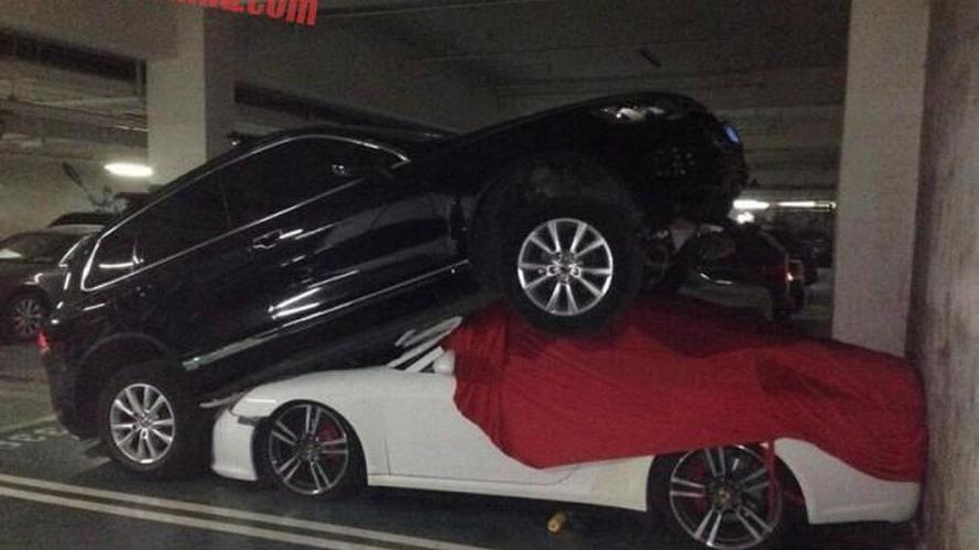 Volkswagen Touareg humps Porsche 911 in parking lot