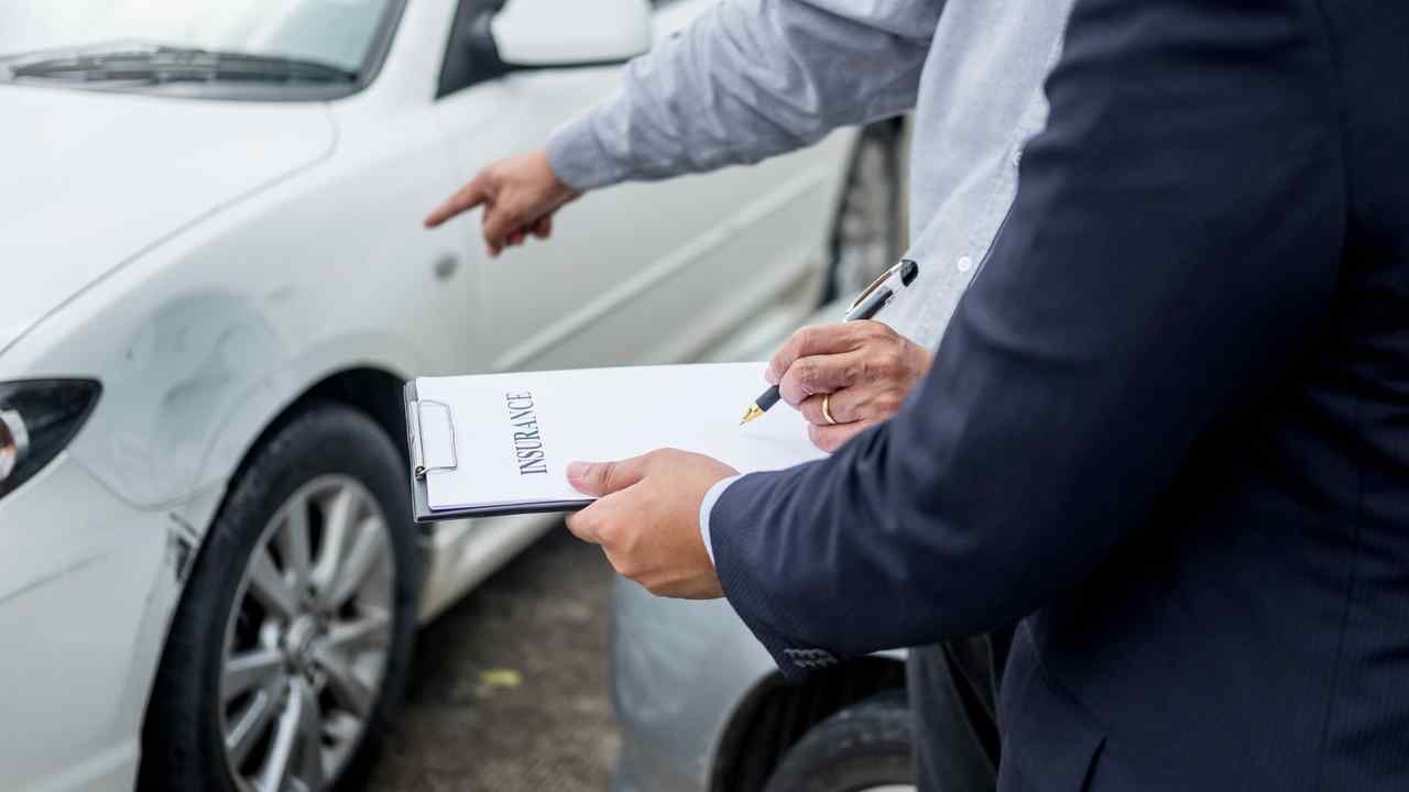 Insurance claims agent examining car after accident