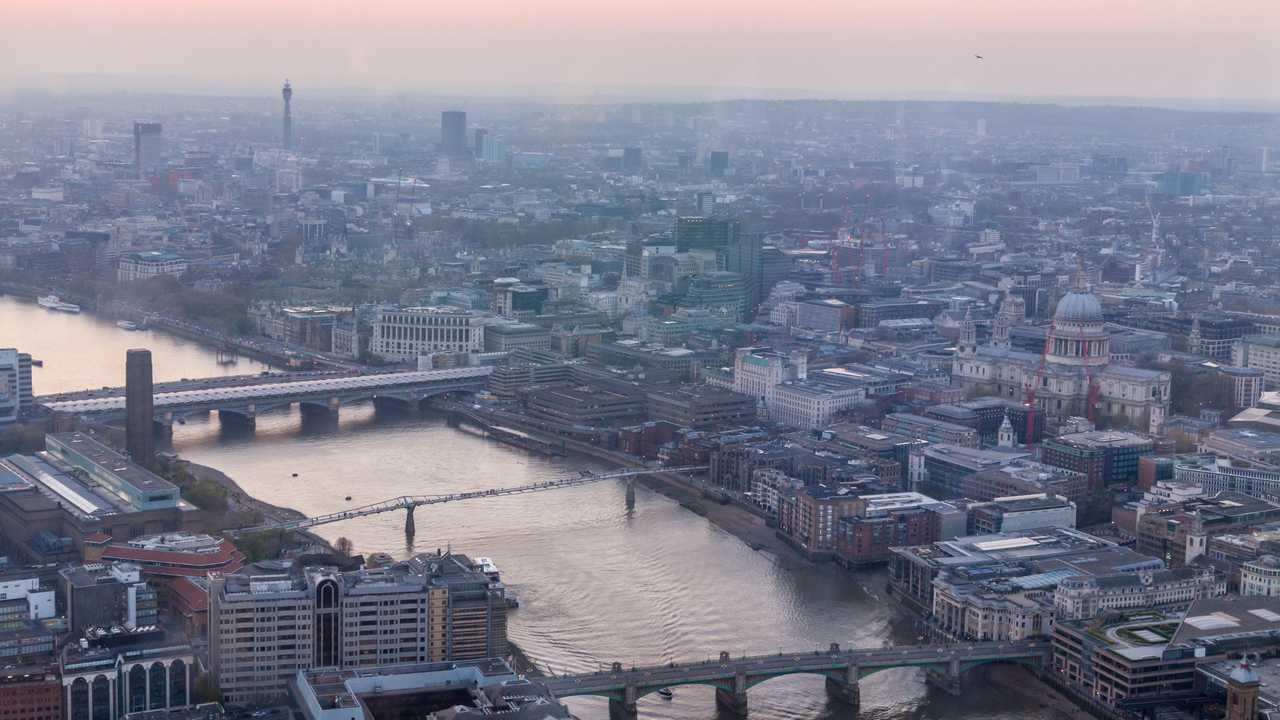 View of Thames river and London at sunset with red sky and air pollution