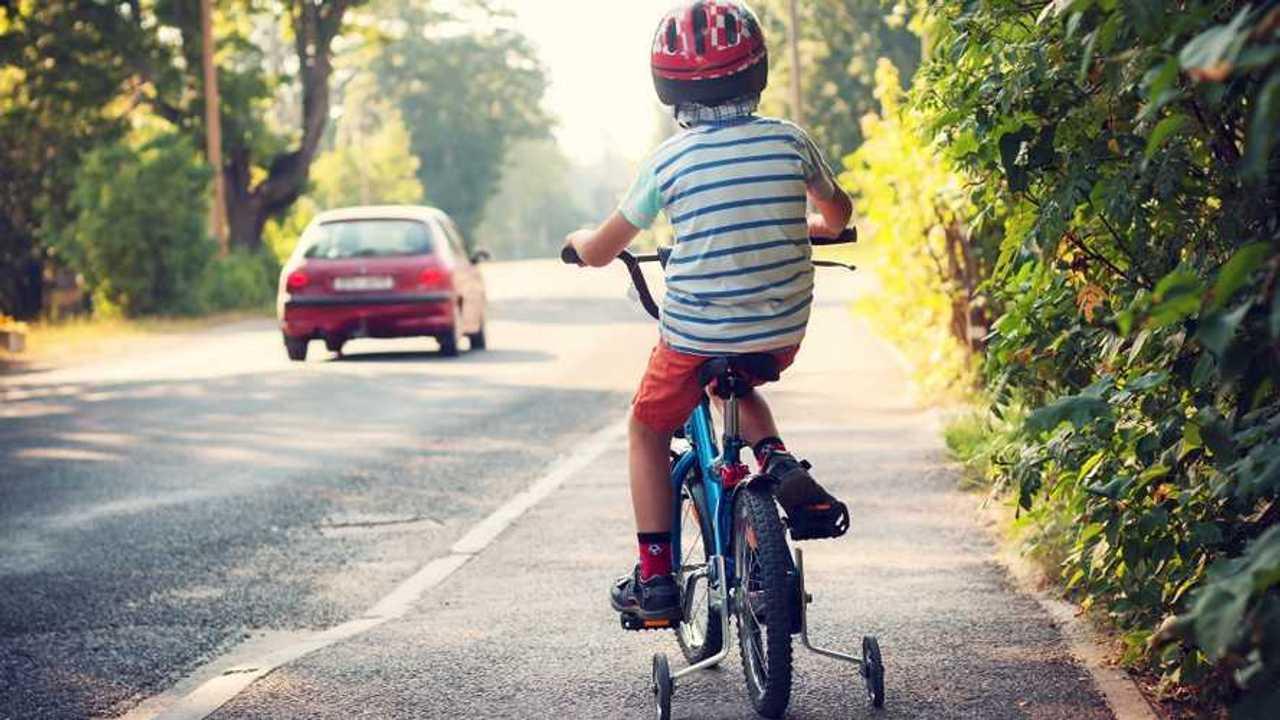 Boy riding bike on pavement sidewalk