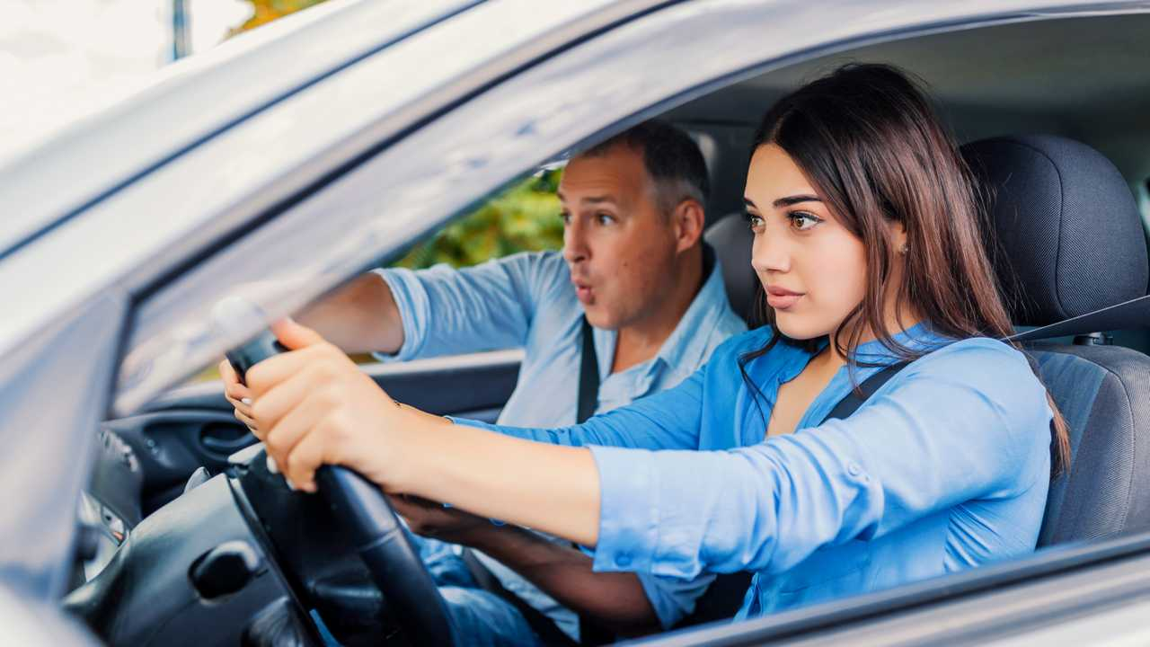 Woman student driver sitting scared in car with instructor