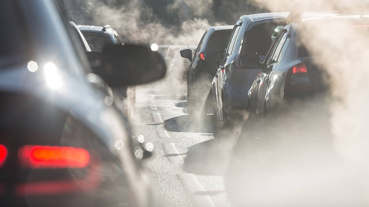 Cars in traffic jam surrounded by exhaust fumes
