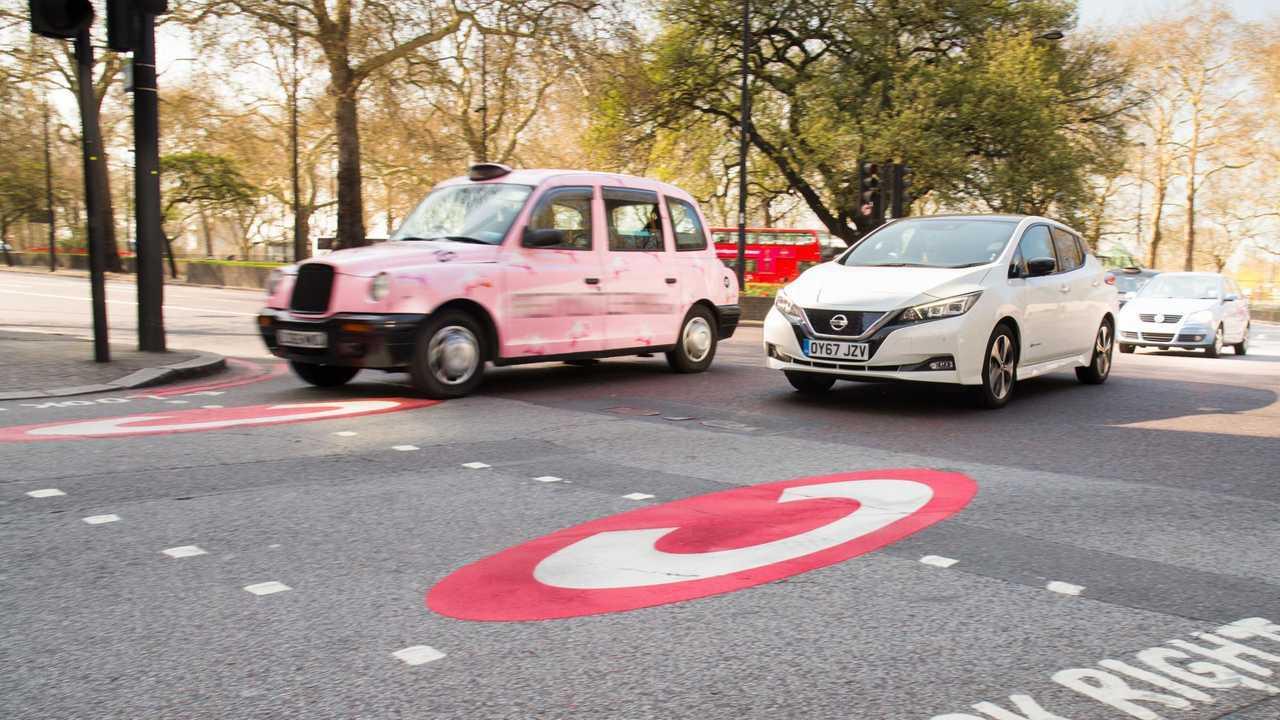 Zona di emissioni ultra basse firmare su asfalto con Nissan Leaf e il taxi di Londra