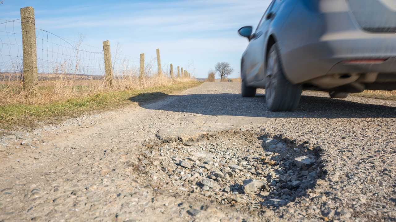 Big pothole on a country road with passing car