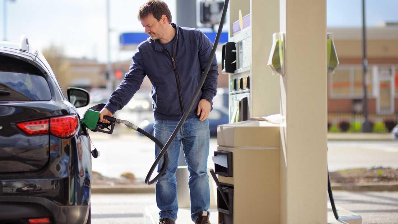 Man filling petrol fuel in car holding pump nozzle
