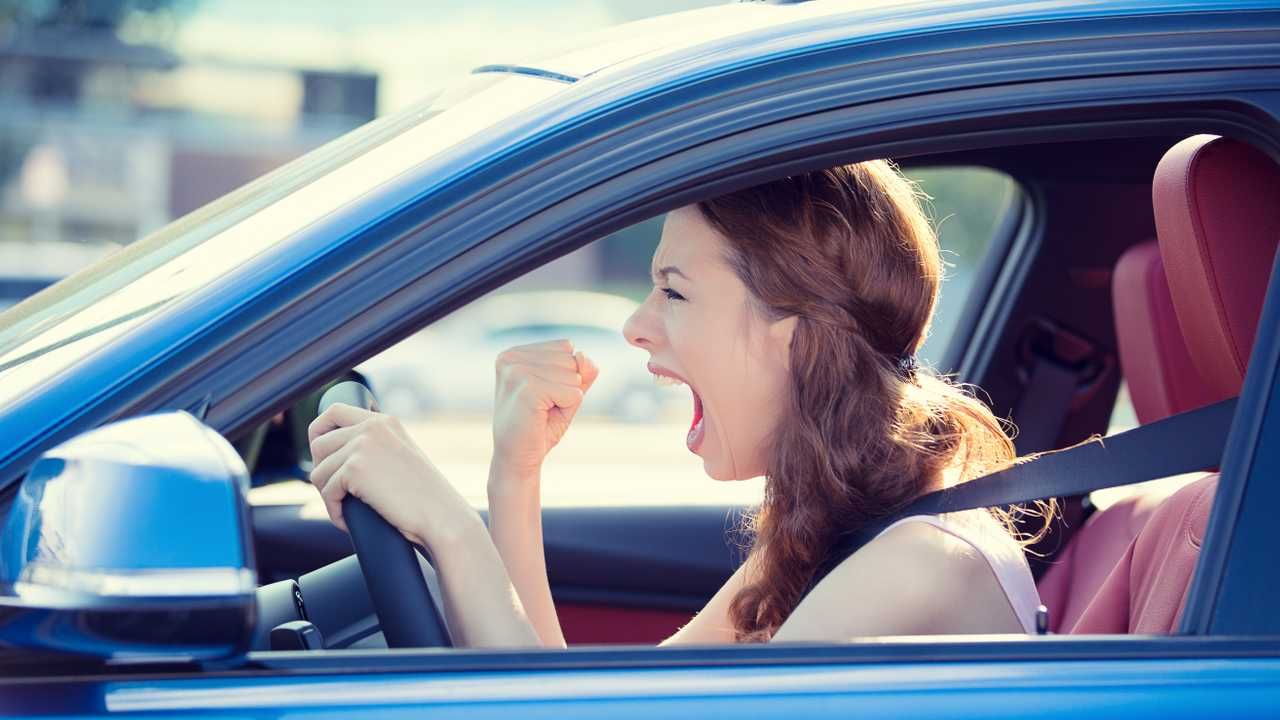 Woman in traffic shouting at someone with fist up experiencing road rage