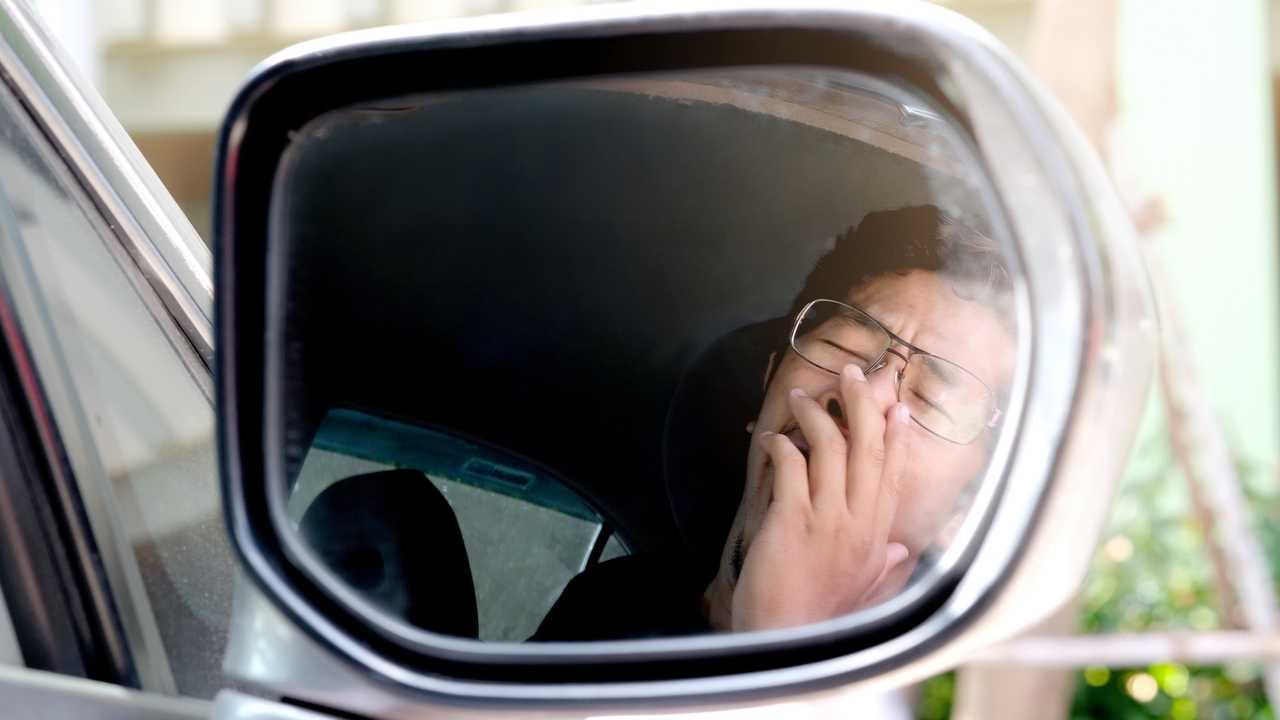 Man drowsy while driving reflection in side view mirror