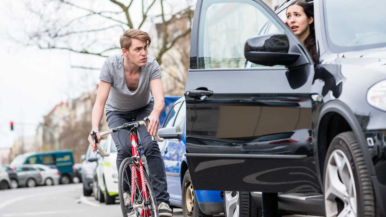 Angry cyclist swerves to avoid opening car door on city street