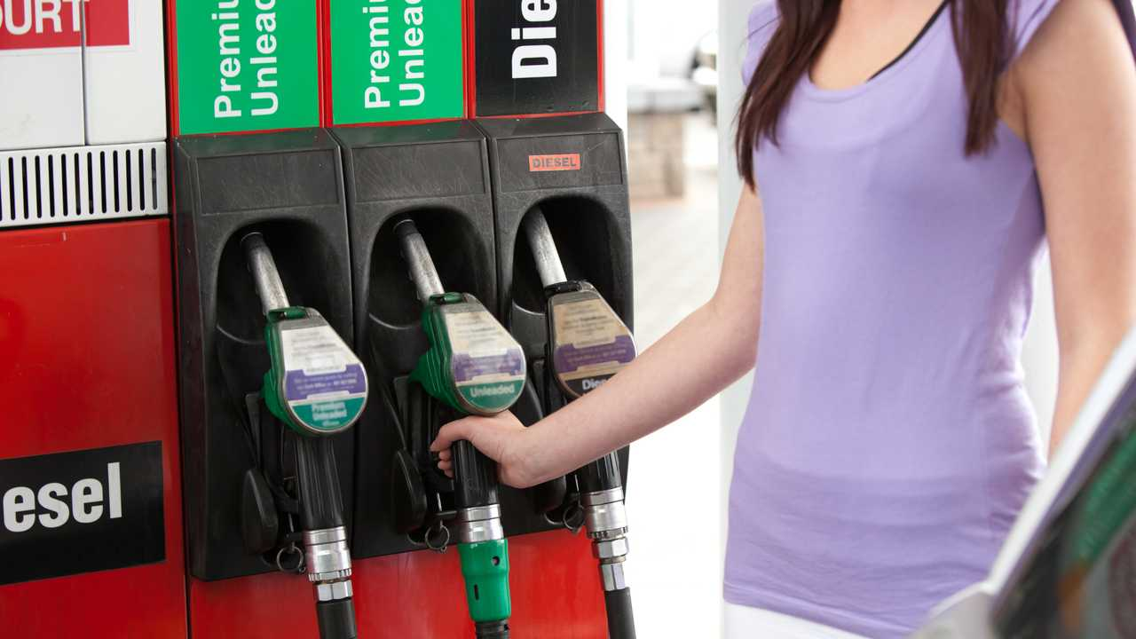 Woman refuelling her car at petrol station