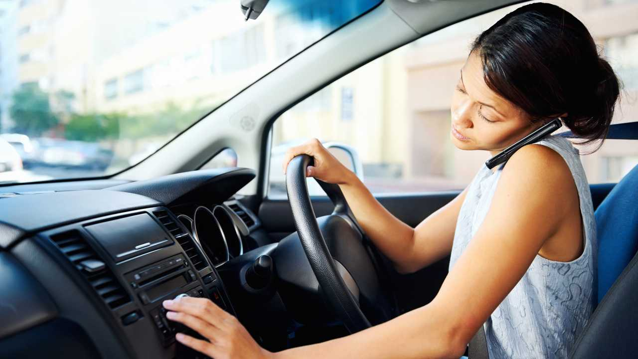 Distracted woman driving car while talking on phone and using radio