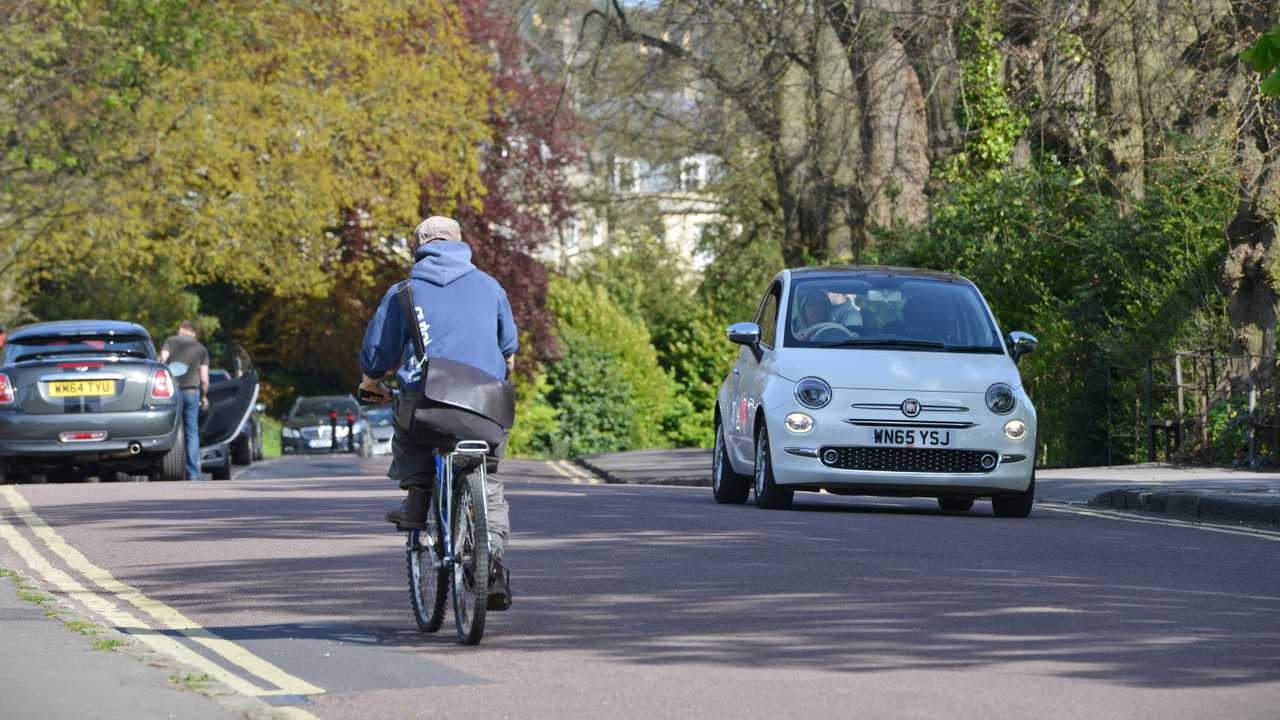 Cyclist and traffic pass through Victoria Park Bath UK