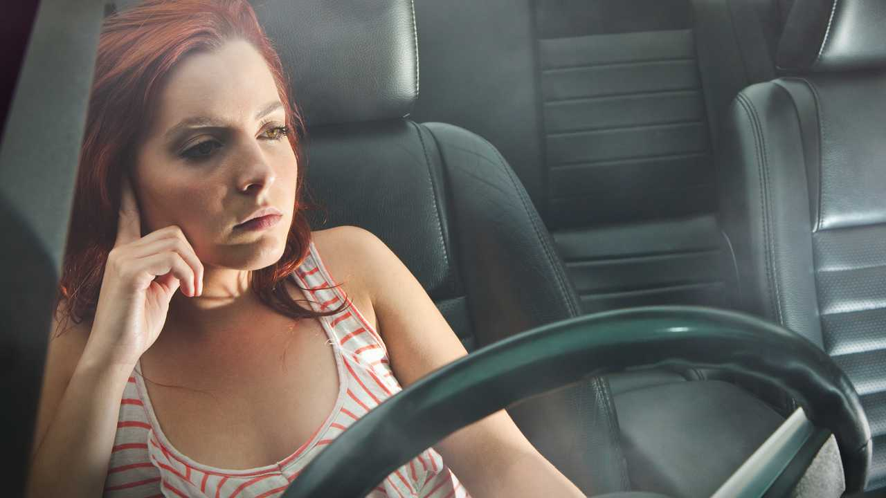 Pensive or depressed young woman behind the wheel driving a car