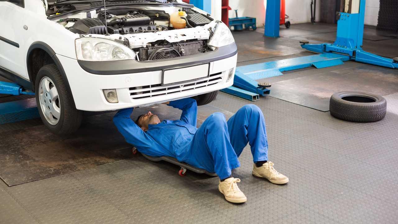 Mechanic working under car at repair garage