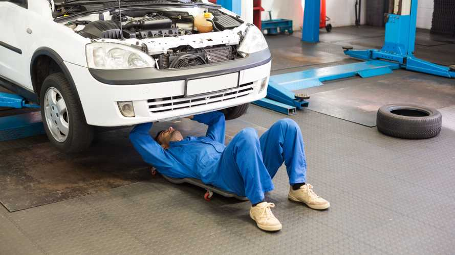 Mechanic working under car at repair garage