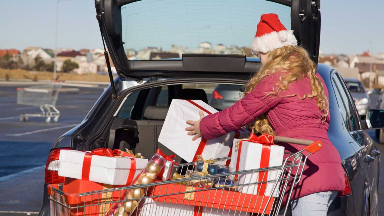 Woman puts Christmas gifts in car boot parked near shops