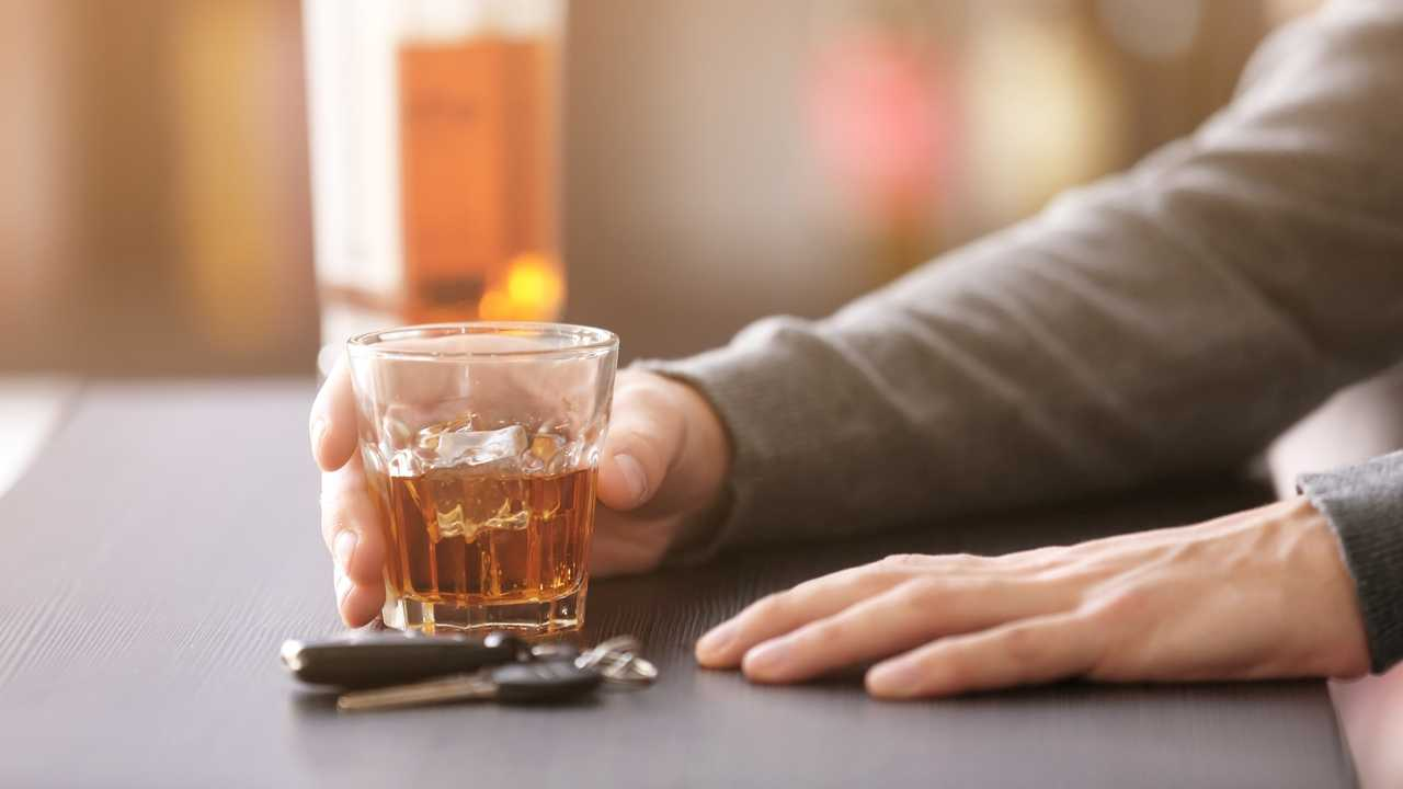 Man sitting at bar with car key and alcoholic drink