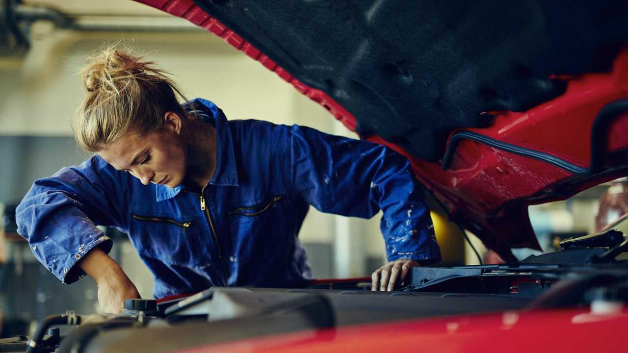 Woman mechanic working on car