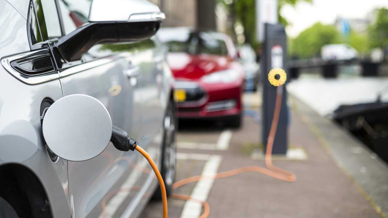 Hybrid car plugged into charging station on street