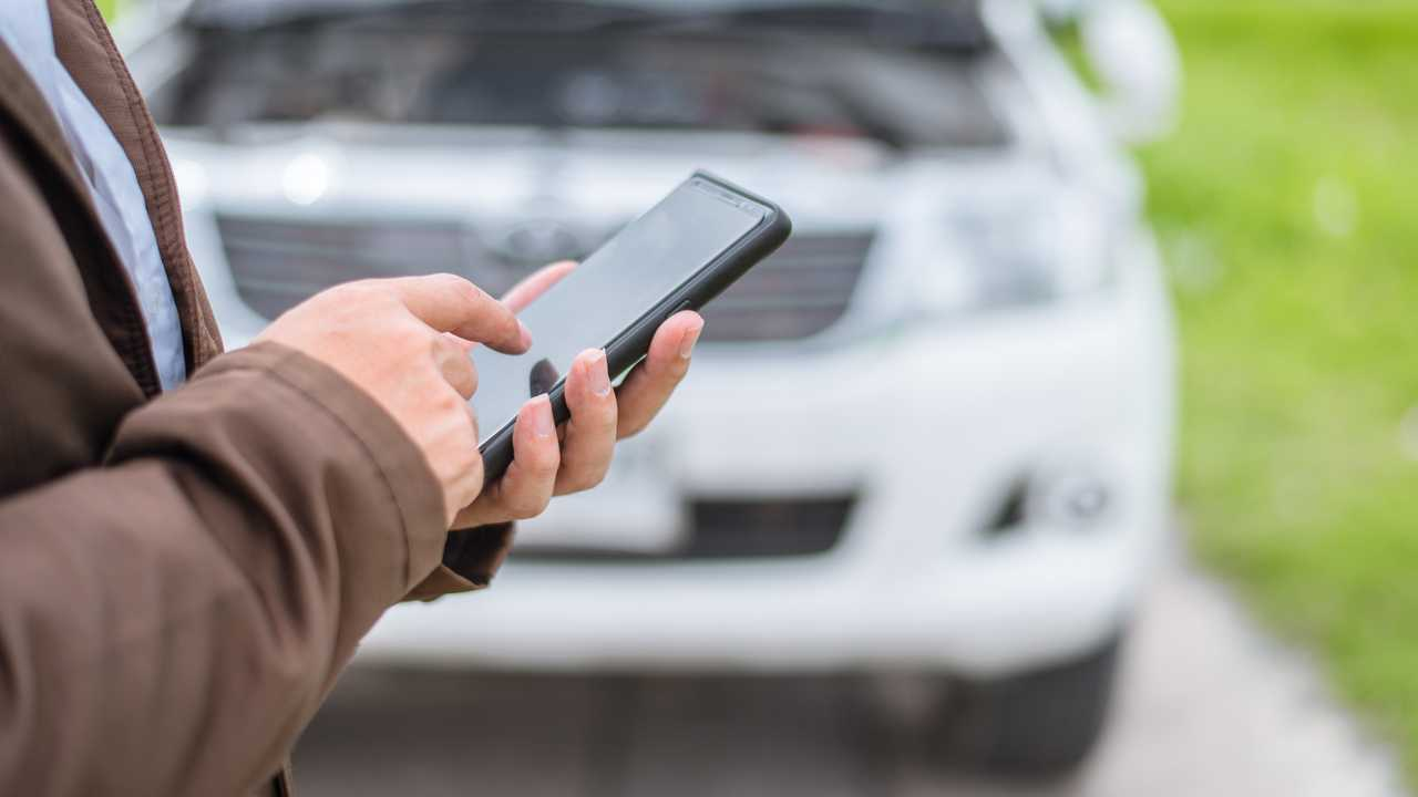 Businessman use smartphone when broken car on the road