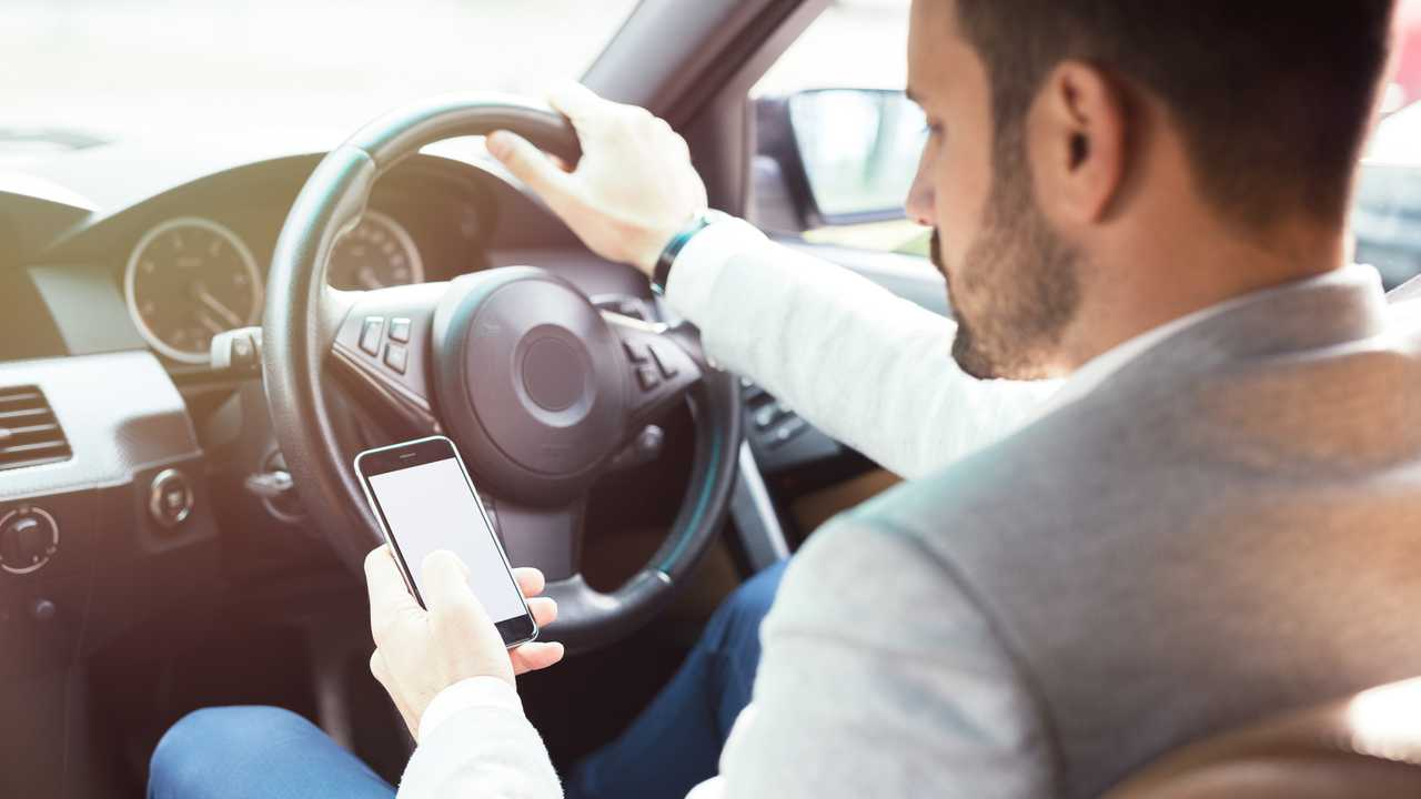 Businessman texting on his mobile phone while driving