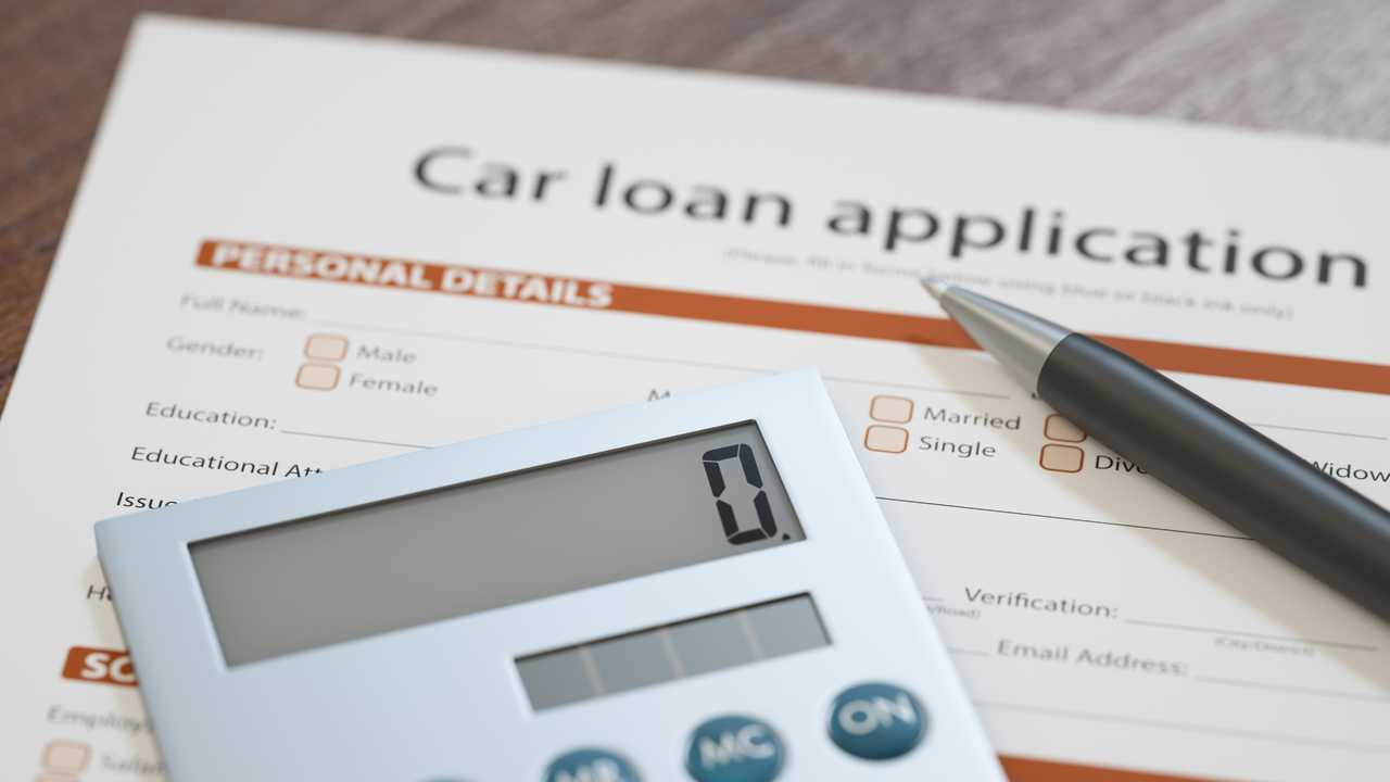 Car loan application with pen and calculator