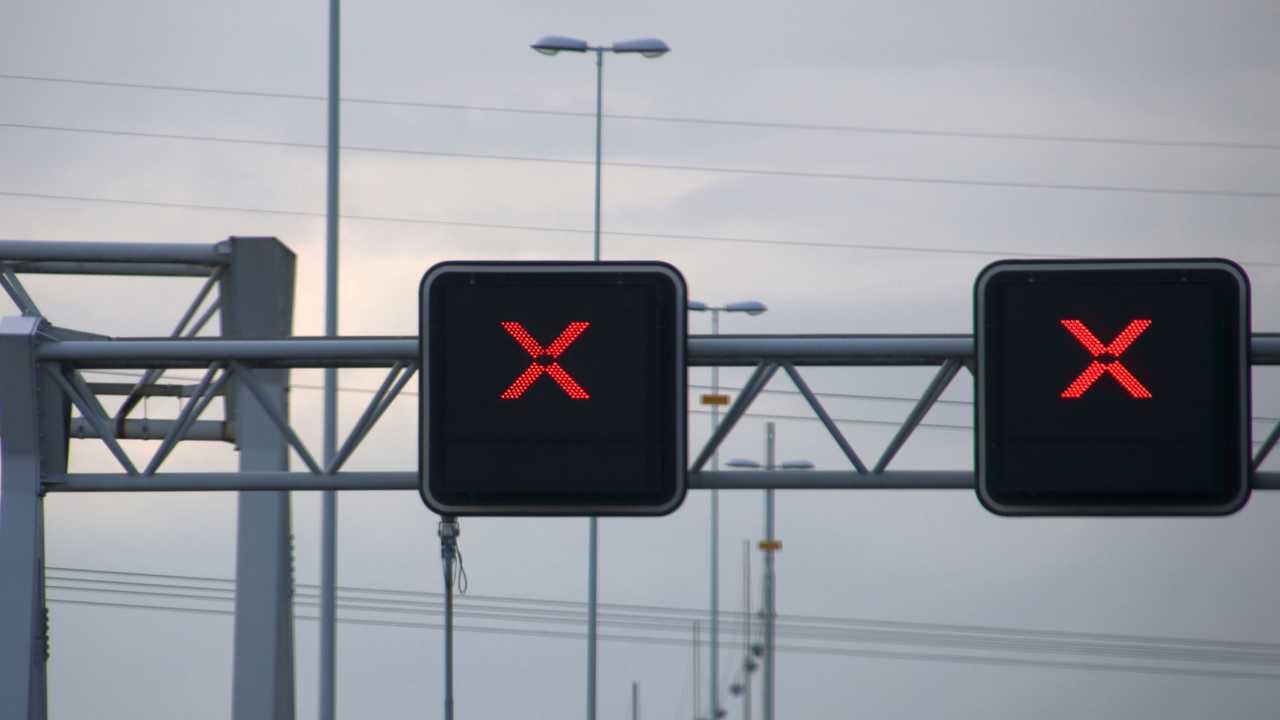 Red cross above lanes on motorway