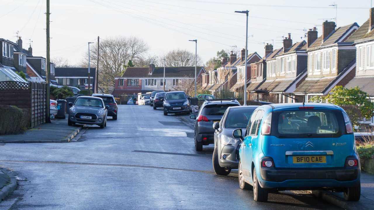 Cars parked on pavement along suburban street in Blackburn Lancashire UK
