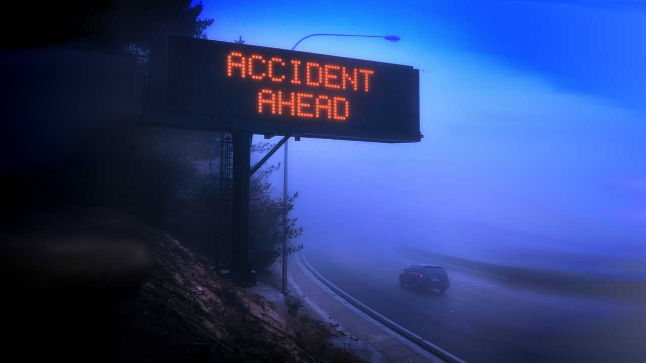 Car driving on foggy highway with digital warning sign showing Accident