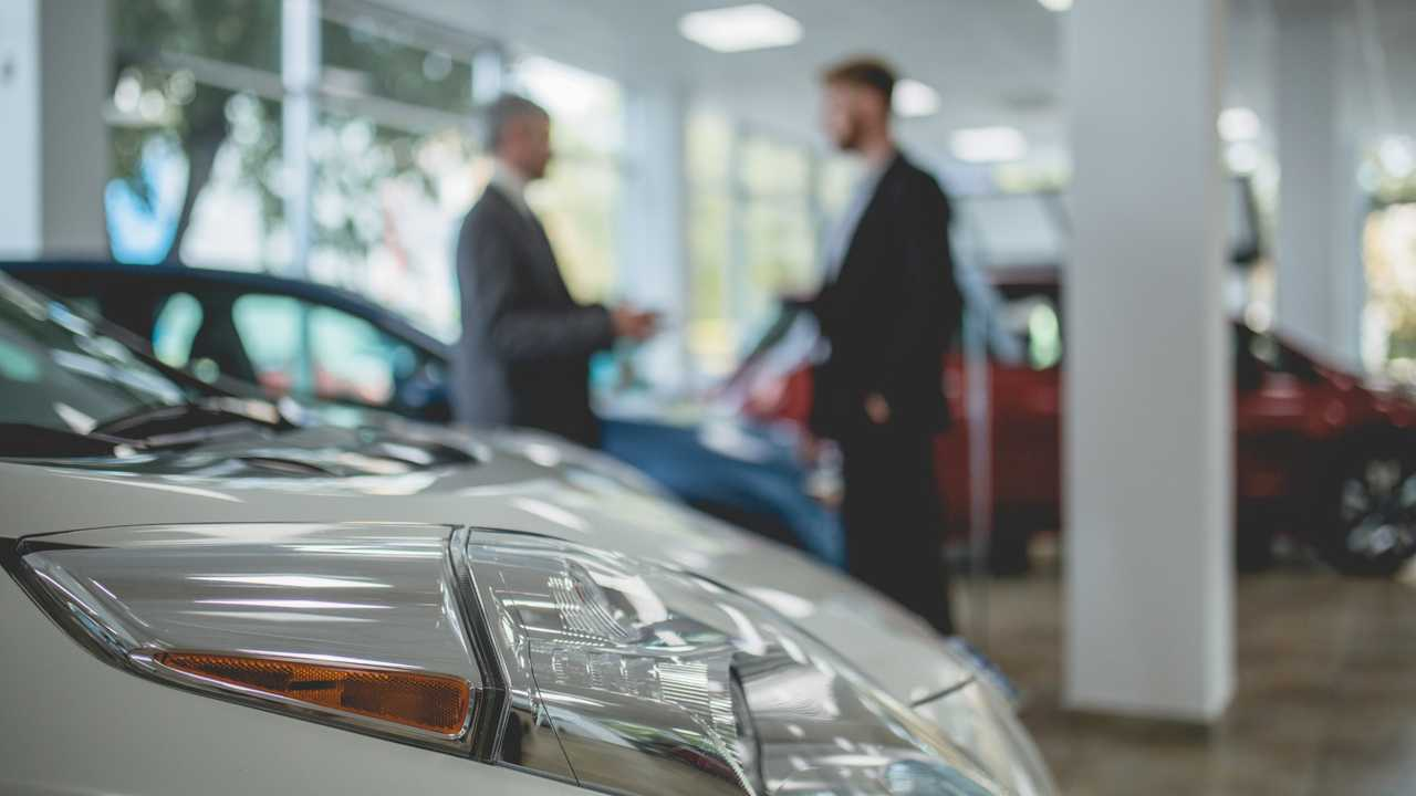 Car salesman talking with buyer in showroom