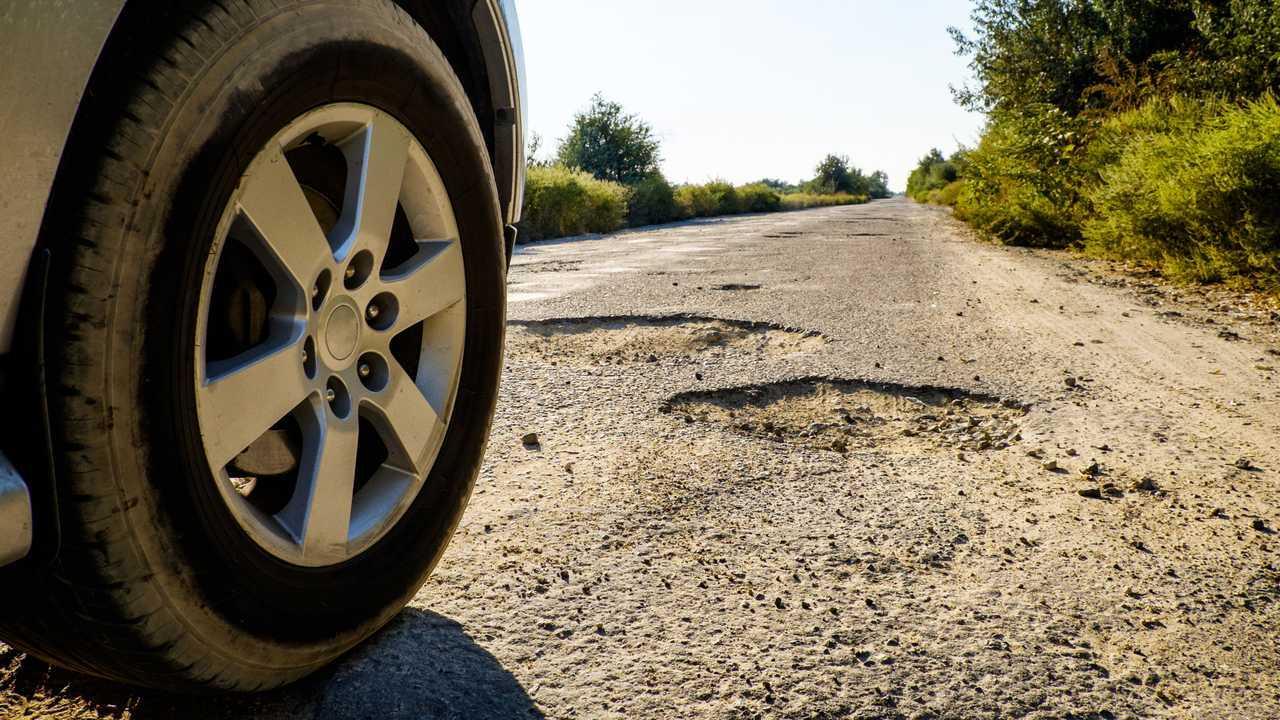Car wheel on damaged road with big potholes