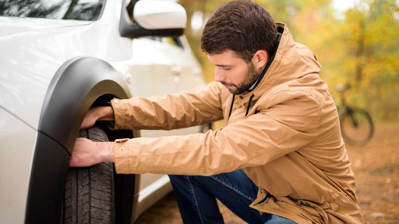 Man checking car tyre