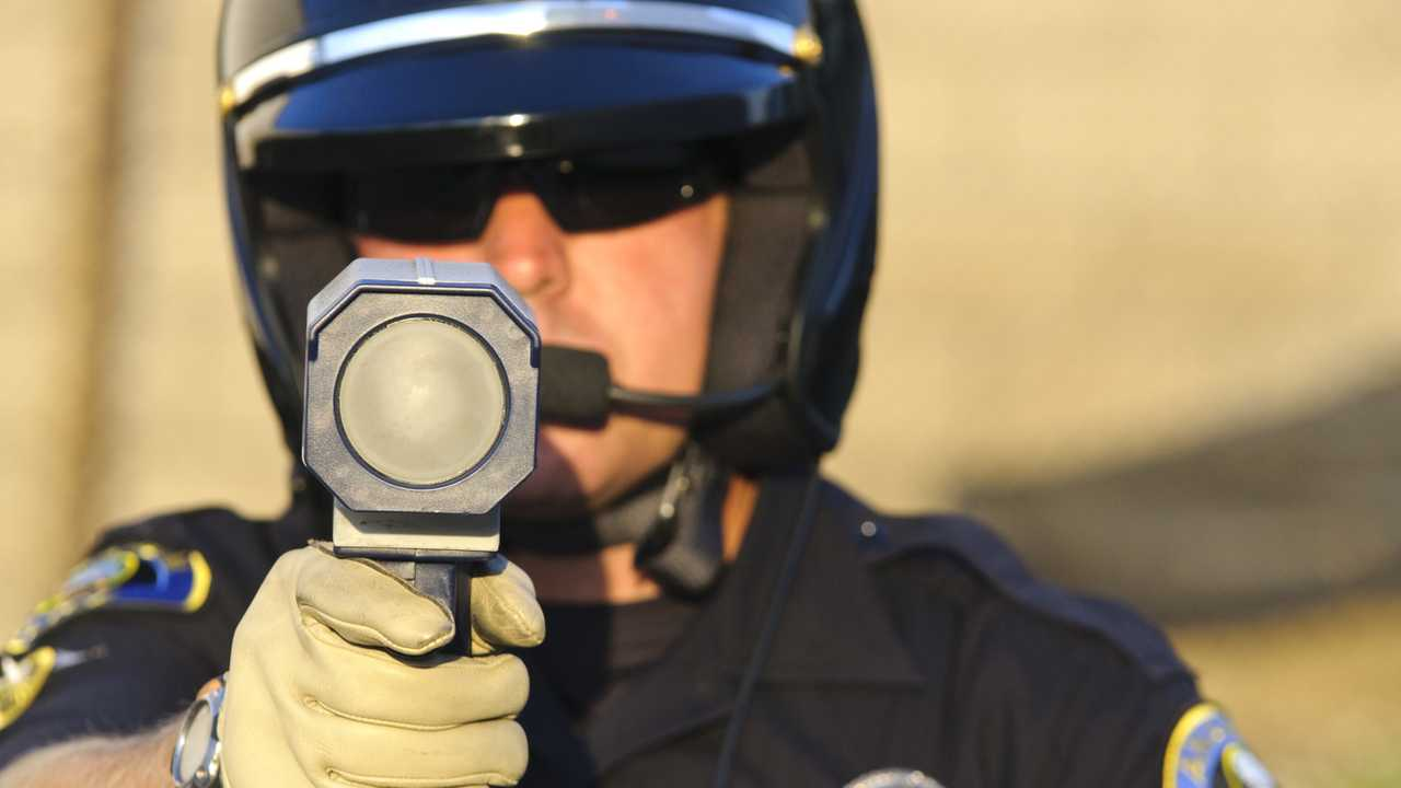 Police officer pointing his radar gun at speeding traffic