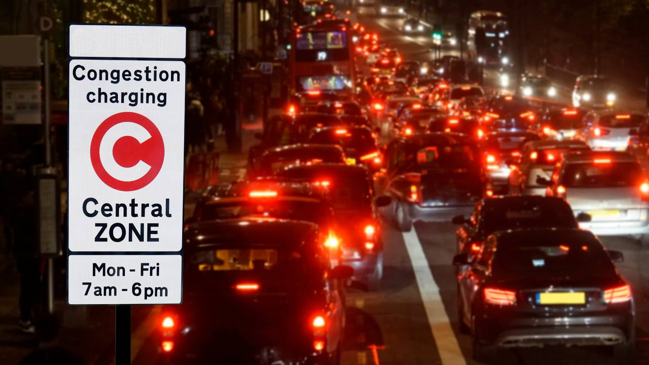 London Congestion Charge Zone Sign over night view of traffic jam