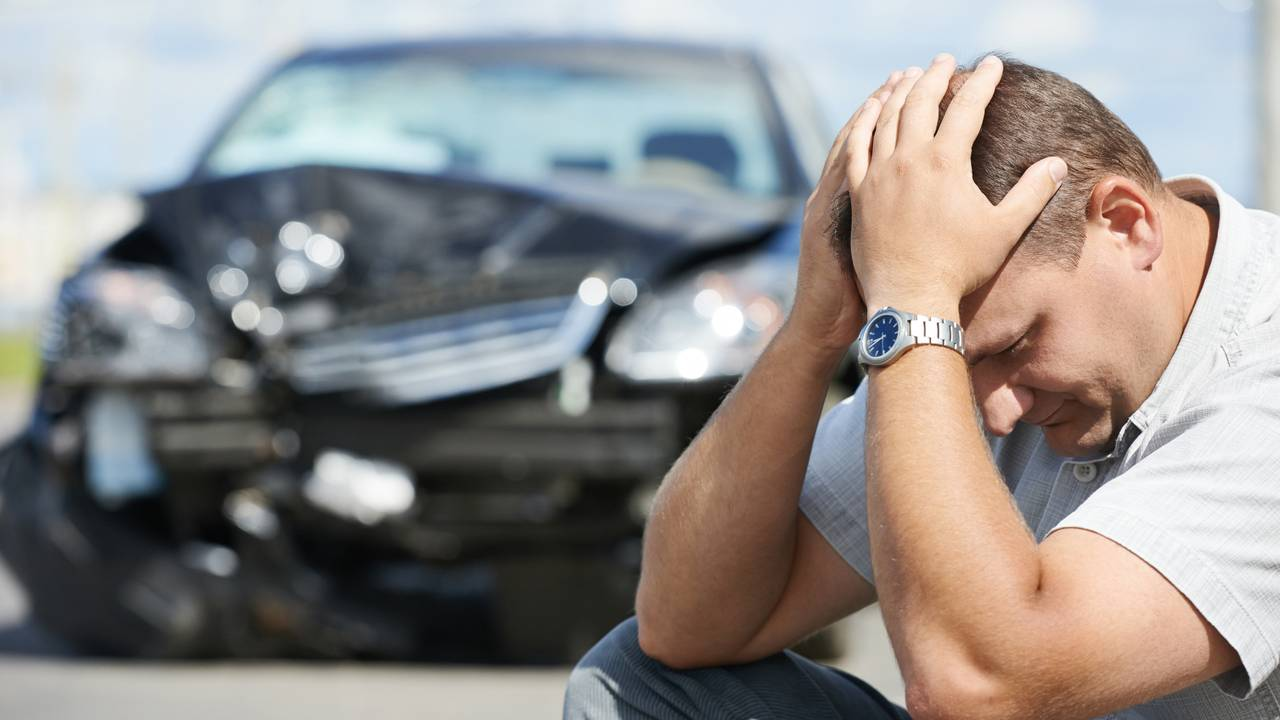 Upset driver sitting in front of car accident on the road