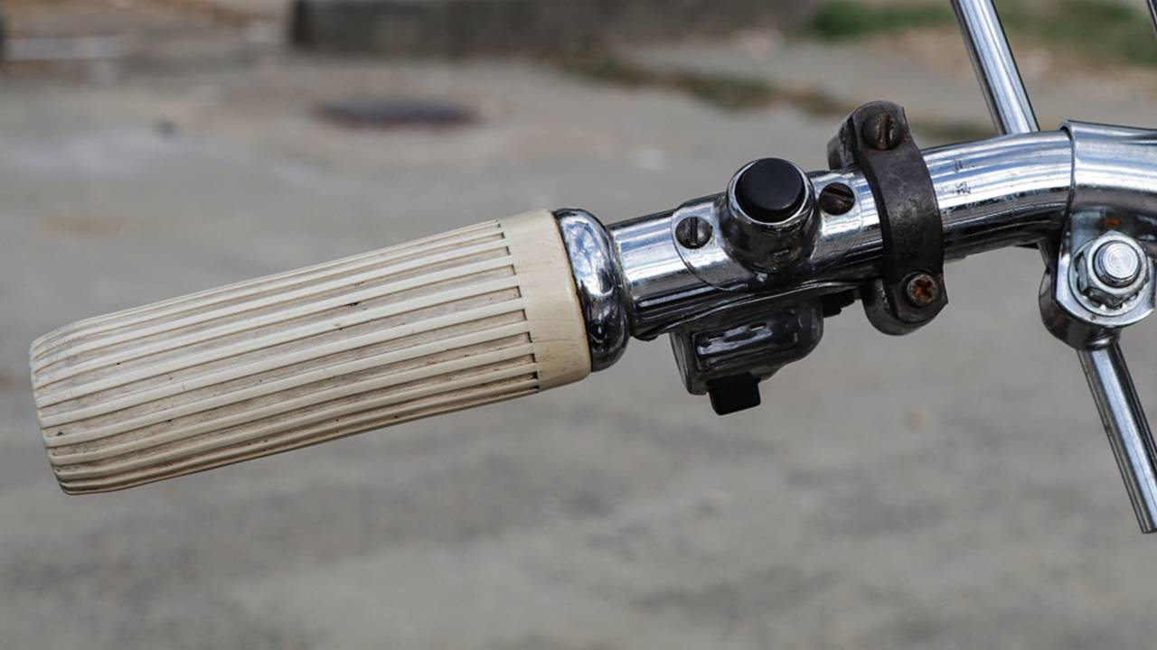 Rotating the left hand grip allows the rider to advance or retard the engine timing. The button operates the horn and the switch controls the hi/low beam.