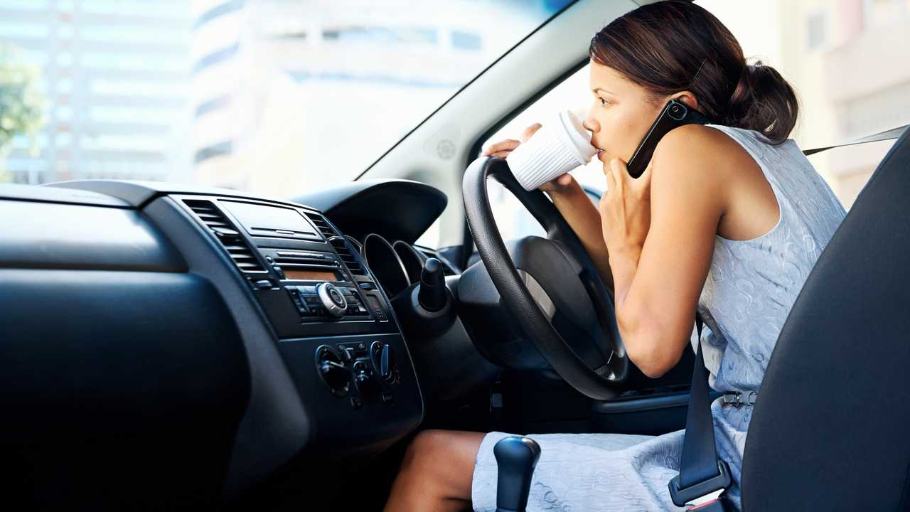 Woman drinking coffee and talking on the phone while driving