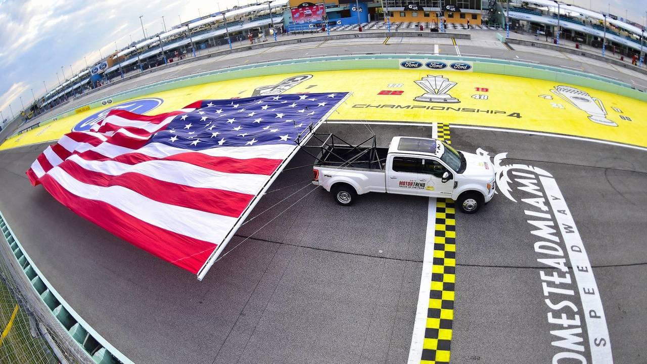 Des Ford & Chevrolet tractent d'énormes drapeaux américains