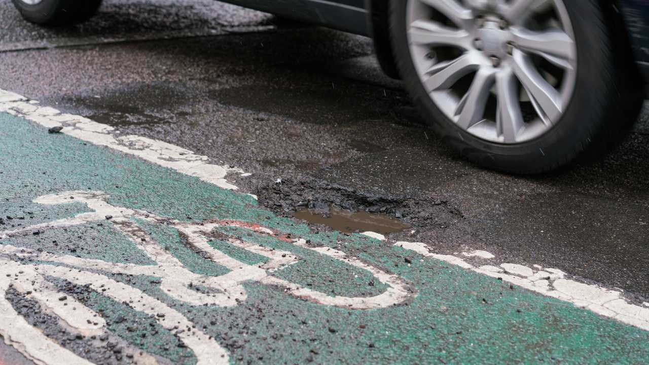 Deep pothole filled with water in Chichester between road and cycle path