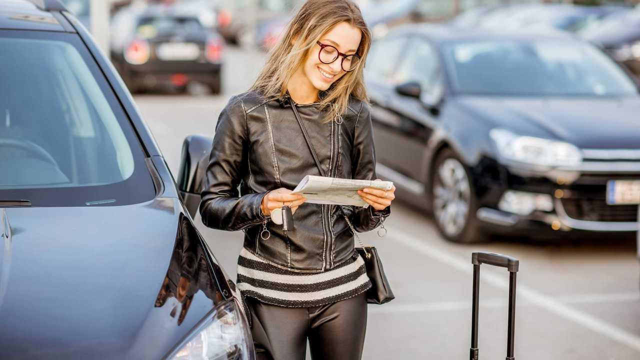 Woman looking at rental contract at airport car park